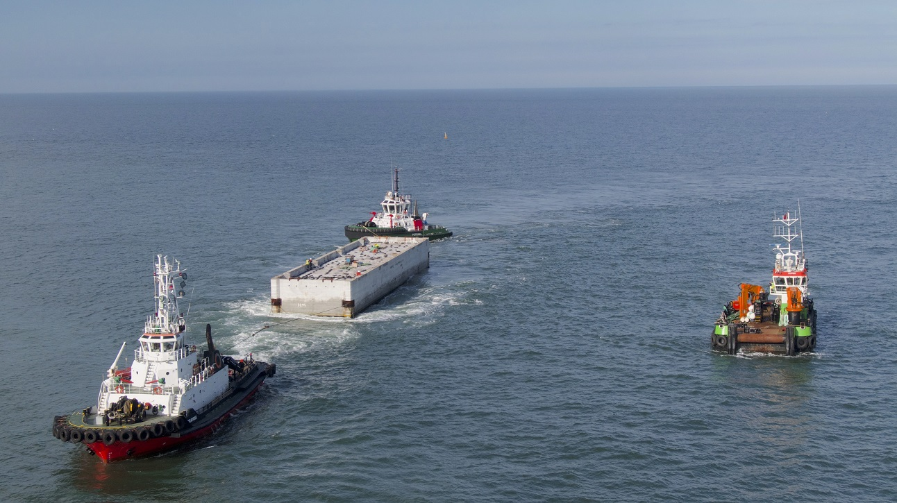 A caisson is towed by a vessel across the North Sea